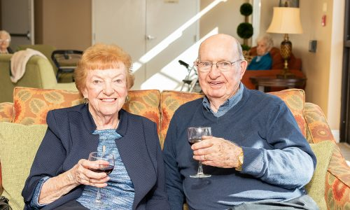 Smiling residents enjoying a glass of wine