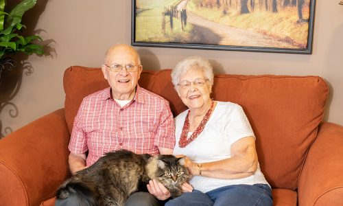 Happy residents sitting on a couch with their cat