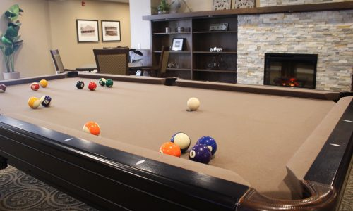 a pool table with pool balls scattered in assisted living bolton