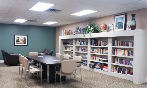a library with a large white shelf and colourful books in assisted living bolton