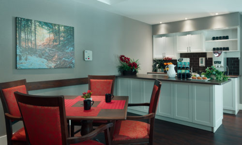 a kitchenette with a table and four red chairs in a retirement home simcoe
