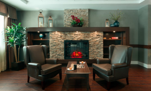 two brown leather chairs in front of a fireplace in a retirement home simcoe