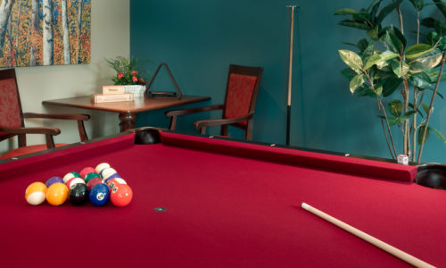 a pool table and chairs in a retirement home simcoe