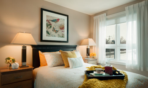 a bedroom with a bright window and yellow blanket in a retirement home in simcoe