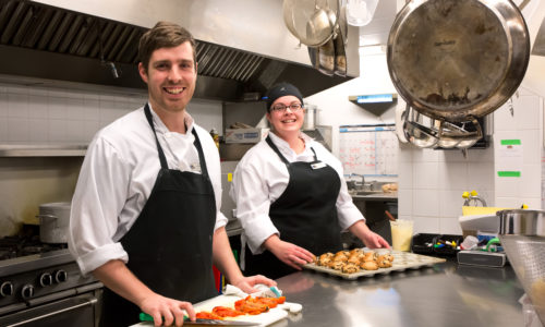 a male chef and a female chef cooking in the kitchen in a retirement home in port hope