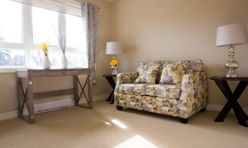 a floral couch with two end tables and a big bright window in a retirement home in port hope