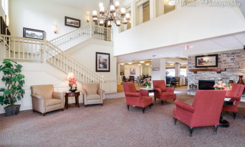 a grand lobby with red velvet chairs in a retirement home in saskatoon