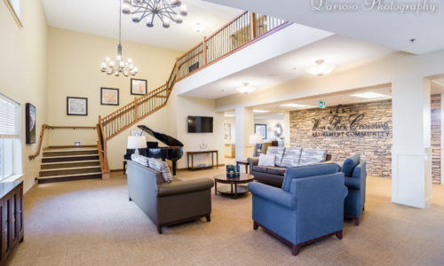 a large lobby with a winding staircase with a brown couch and two blue chairs in a retirement community moosejaw, retirement home moosejaw, assisted living moosejaw, dementia care moosejaw