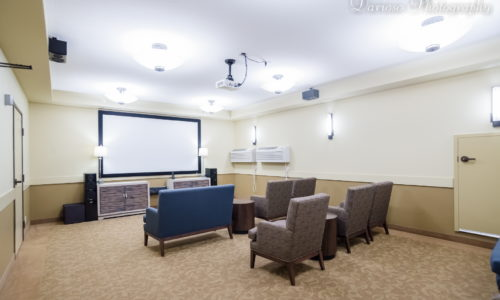 a movie theatre room with a blue couch and brown chairs in a retirement community in moosejaw